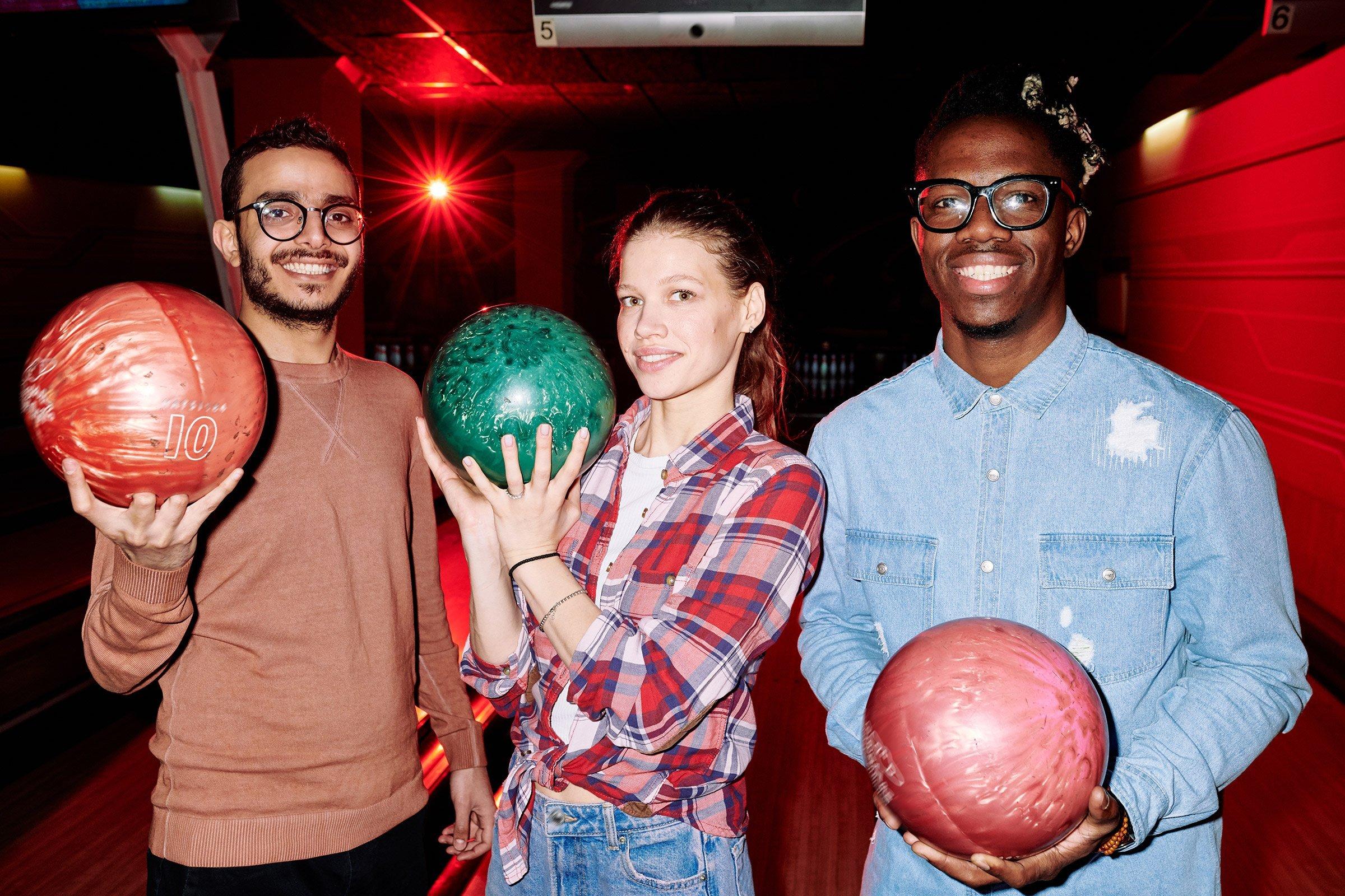 friends holding bowling balls