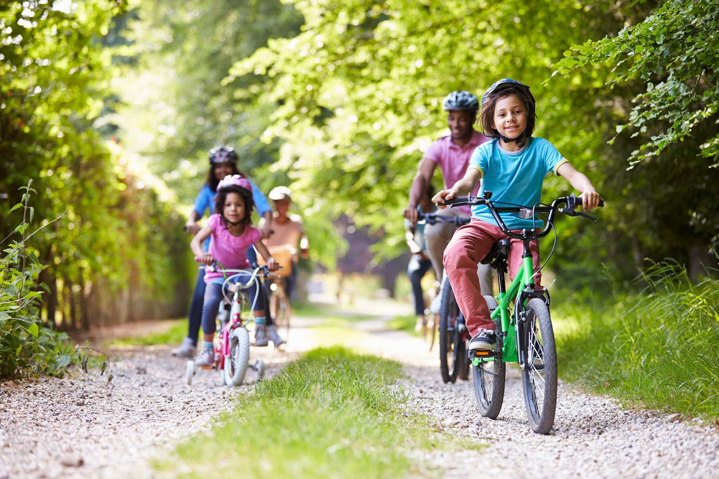 parents and children riding bikes on a gravel path